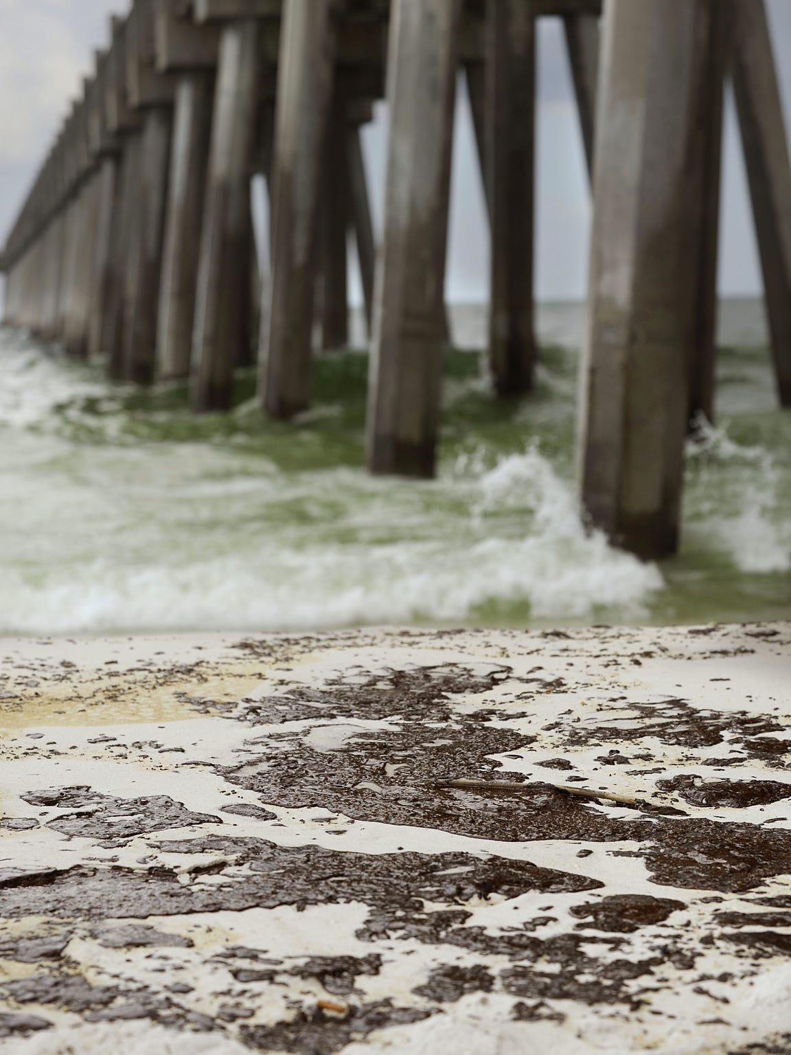 Mats of oil from the Deepwater Horizon oil spill washed ashore along Pensacola Beach on June 23, 2010, just east of the Pensacola Beach Gulf Fishing Pier. The Senate passed a bill Monday that would allocate $300 million to eight Northwest Florida counties.