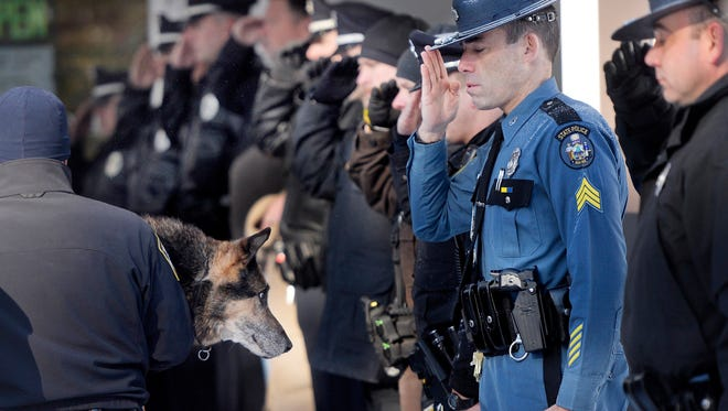 In this Feb. 13, 2015, photo Sgt. Robert Burke of the Maine State Police salutes along with other officers from local communities as Canine Officer Shane Stephenson of the South Portland Police Department carries Sultan, a retired police dog into the Yarmouth Veterinary Center where he was euthanized in Yarmouth, Maine. Dozens of officers and firefighters turned out this month to pay their respects to Sultan, a 13-year-old German shepherd who sniffed out drugs and bad guys with the Yarmouth Police Department.