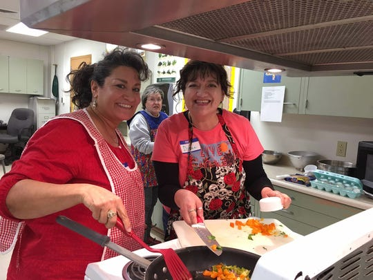 Nancy Lynn Lucero, left, and her sister Diane Madrid prepare quick and easy Spanish eggs during a recent Kitchen Creations cooking school for adults with diabetes. Their mother Jane Madrid, background, also attended the cooking school.