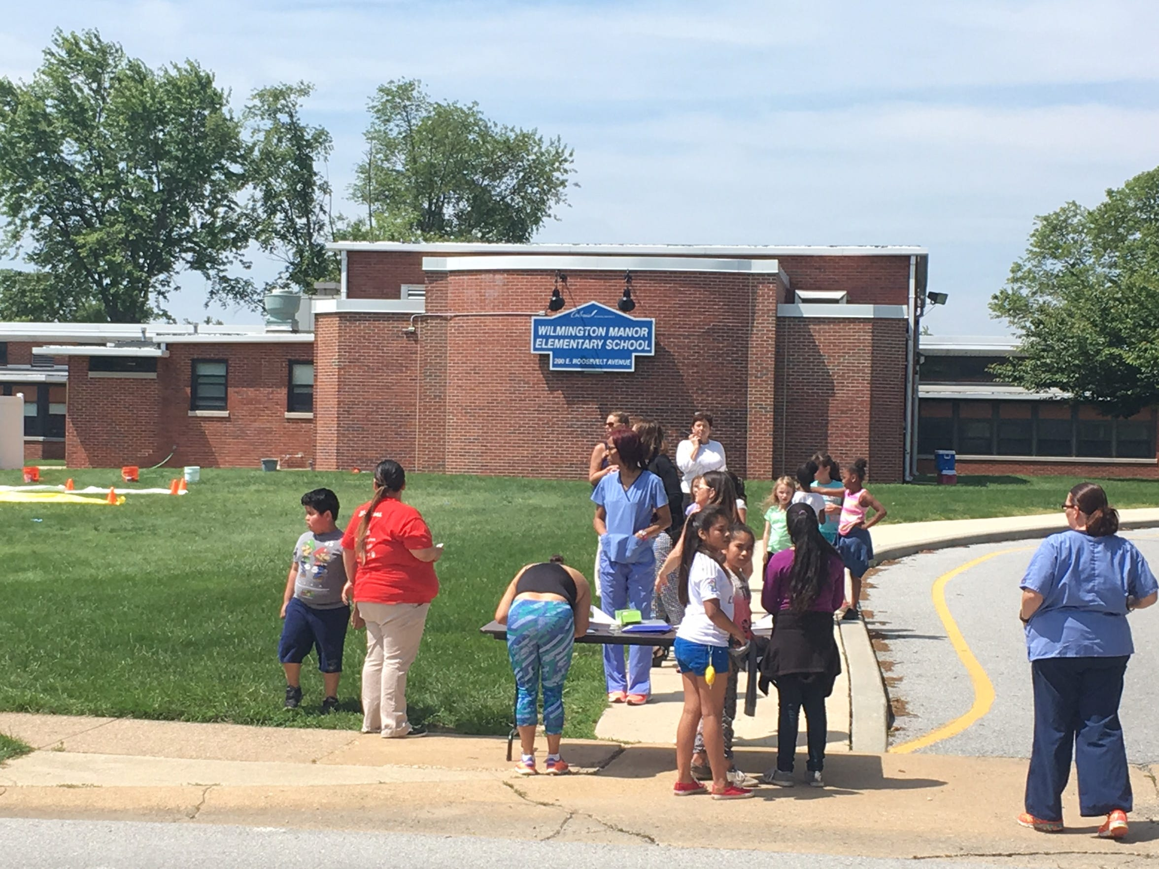 Parents sign their children out of Wilmington Manor Elementary School after it received a bomb threat Wednesday morning.