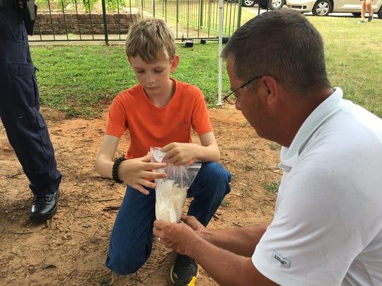 Prattville PD investigator Tom Allen shows Travis Haslam how to make plaster casts of footprints.