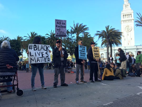 Protesters hold signs in solidarity with the Black