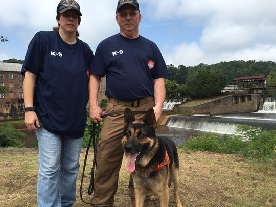 Sherry and Fabian Mann pose with Remi, the search dog that leg rescuers to a group that became stranded on  Autauga Creek.