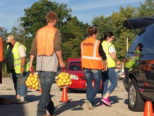 A volunteer carries bags of lemons to a waiting vehicle
