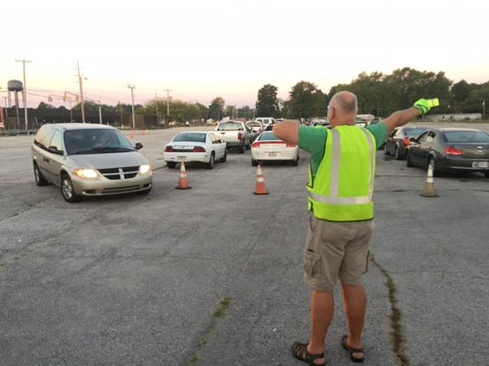 Steve Watkins, a volunteer for Second Harvest Food Bank, directs traffic before the start of a tailgate food distribution event.
