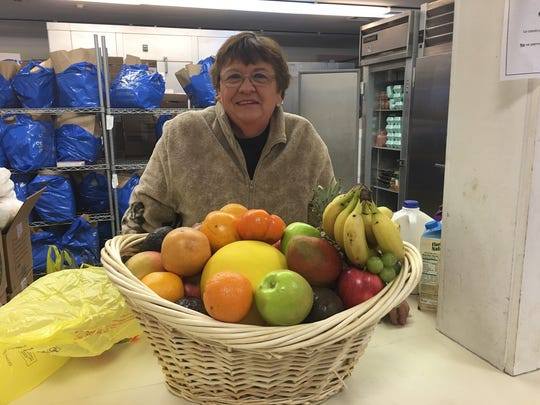 Betty McGuinness, a volunteer at the Franklin Food Bank, prepares to distribute donated produce.