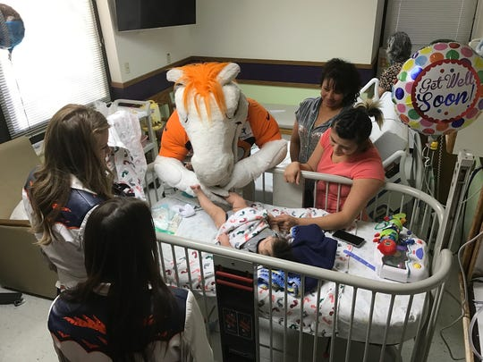 Miles and two Denver Broncos cheerleaders visit 3-month-old Gabriel Alvarez at Poudre Valley Hospital on Nov. 16. The Broncos crew visited patients at both PVH and Medical Center of the Rockies to spread Broncos Fever and good cheer.