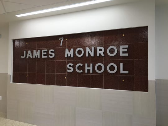 The entrance to the new James Monroe School features the original school sign salvaged from the March 2014 fire that destroyed the building.