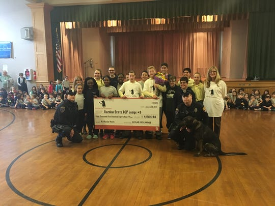 Our Lady of Good Counsel School students hold a check
