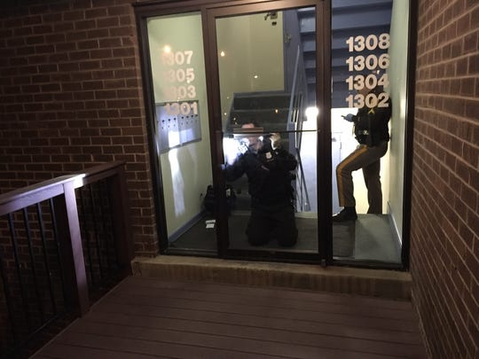 New Castle County police on Monday evening examine a door at the Bluffs apartments in Pike Creek after a man tried to abduct a woman there.