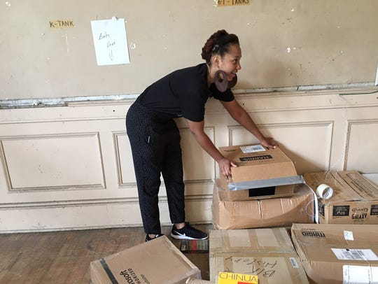 Shonte Smith, 24, of Plainfield stacks up boxes of