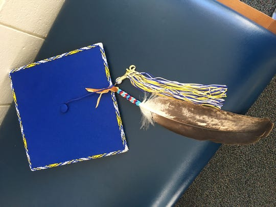 A graduation cap with an eagle feather attached.