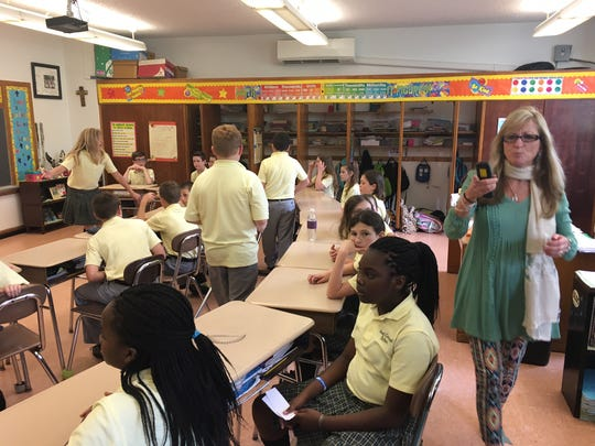 Our Lady of Good Counsel School teacher Marcie Steel walks in her classroom on Wednesday afternoon as students prepare to hear a presentation from PSE&G. Her students wrote letters to the company's CEO suggesting ways the company could use more renewable energy.