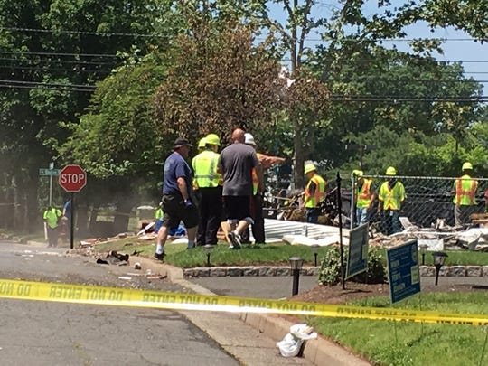 Utility and emergency personnel check the site of a Piscataway house explosion.