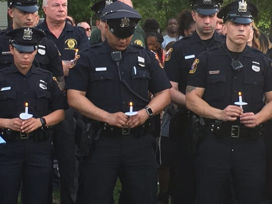 Linden officers stand with candles lit at Tuesday night's vigil.