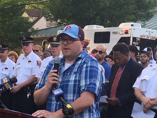 Adam Kuczynski, brother of Officer Daniel Kuczynski, speaks during a candlelight vigil for  his brother.