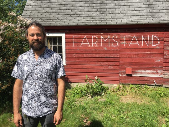 Ryan Miller stands outside his farm stand in New Haven,