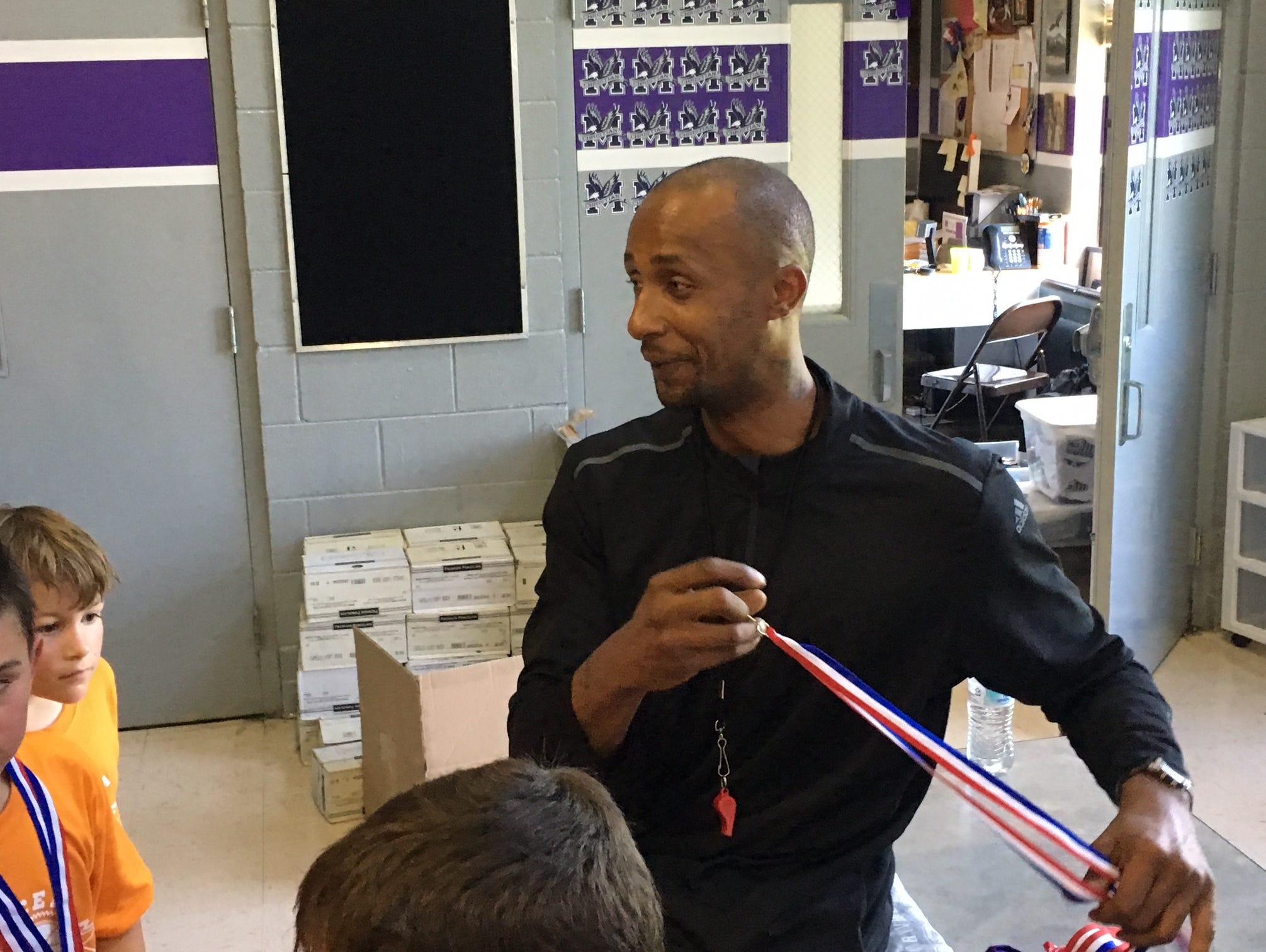 Former Vols basketball star Vincent Yarbrough hands out medals at a camp at Maryville Christian School.