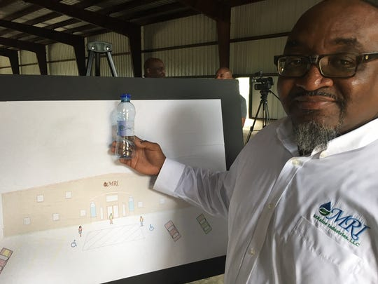 Marquis Forge, CEO of MRaine Industries LLC, holds a bottle that will be used in the Autaugaville bottled water plant.