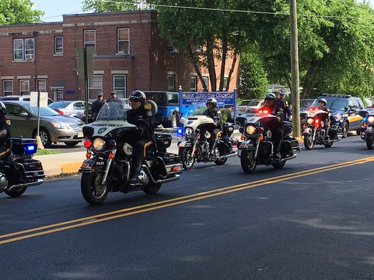 Police on motorcycle lead the funeral procession to