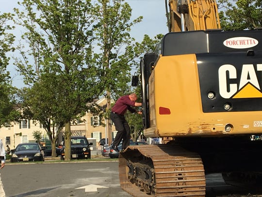 Dover Mayor James Dodd climbs aboard a CAT excavator