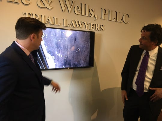 Attorneys Aaron Neglia (left) and Murray Wells with Horne & Wells PLLC discuss a photo of the front door of Ismael Lopez's home.