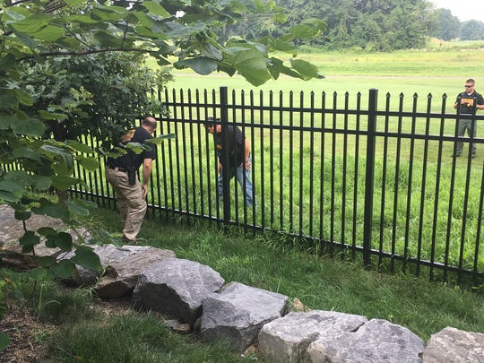 New Castle County police officers search the Ed Oliver Golf Club near Wilmington for additional evidence following the shooting.