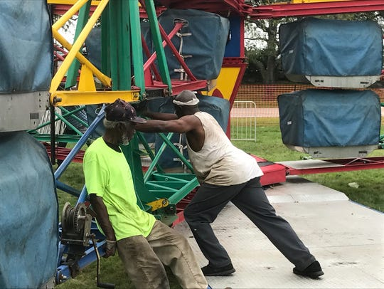 Crews setting up a ride called The Scrambler at the