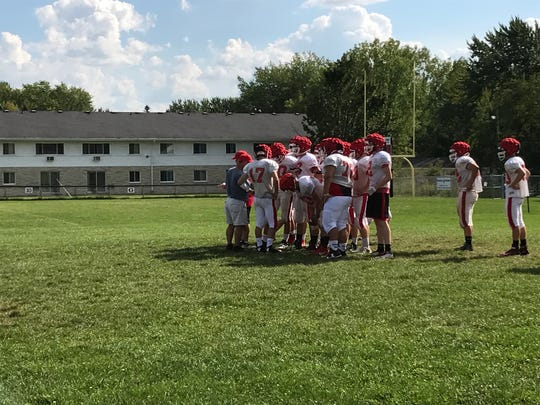Pacelli players huddle together before splitting off for positional drills during a recent practice in preparation for the 2017 season which kicks off this week.