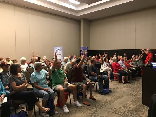 Former K-25 site workers raise their hands at a town hall-style meeting with the Cold War Patriots, a medical advocacy group for plant workers.
