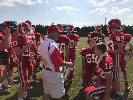 Pacelli offensive coordinator John Raflik huddles with
