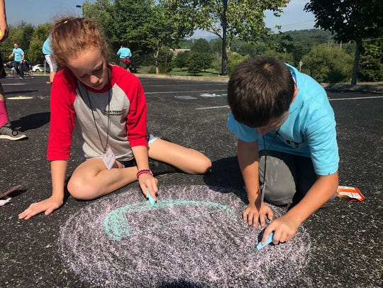 Parker Mease and Josie Cromer color in a chalk drawing