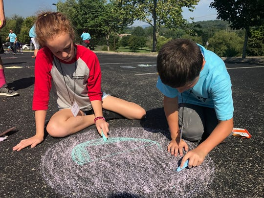 Parker Mease and Josie Cromer color in a chalk drawing of Charon, one of Pluto's moons, at an Oak Ridge Associated Universities eclipse viewing event for area Boys and Girls Clubs on Monday, Aug. 21, 2017.