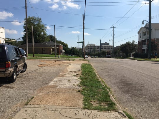 The sidewalk in front of a corner store with the Memphis VA Medical Center in the distance.