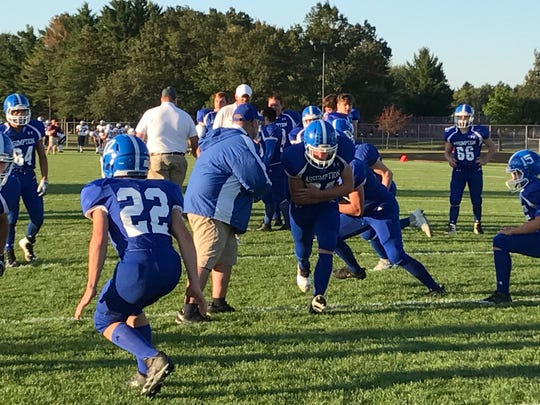 Members of the Assumption offensive backfield run through some plays prior to kickoff against Loyal at South Wood County 2000 Football Field on Thursday night.