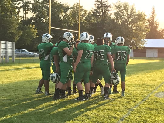 Almond-Bancroft linemen huddle up prior to the opening kickoff of their Central Wisconsin Conference-Small opener with Wild Rose on Friday night.