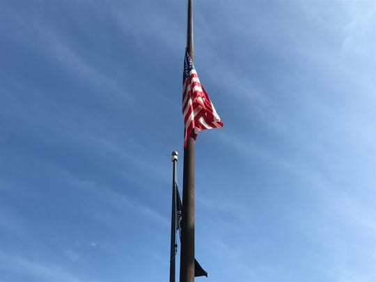 The flag flies at half-mast in front of Passaic City
