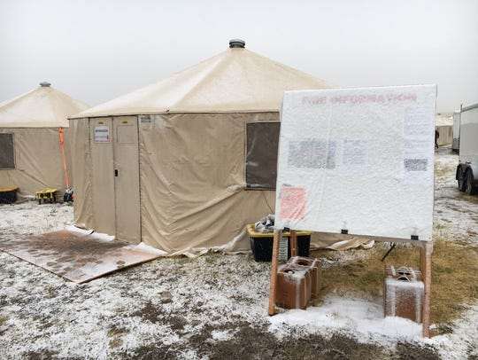 Snow covers up the fire information board at fire camp