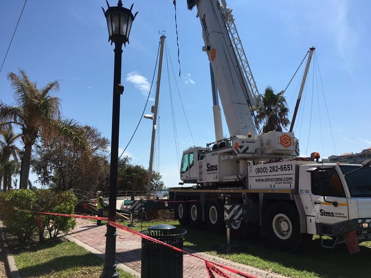 Crews lift two sailboats from the Indian River Lagoon near Cocoa Village.