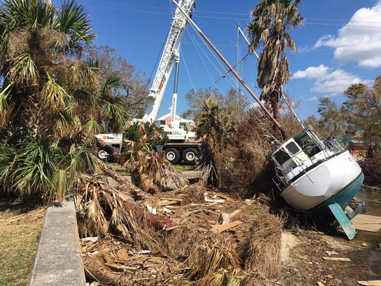 Crews lift two sailboats from the Indian River Lagoon
