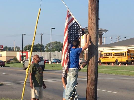 Matt Sauer, right, David McGruder, center, Bennie Stone, left, fix upside an down flag Tuesday morning at Christian Community Outreach in Henderson.