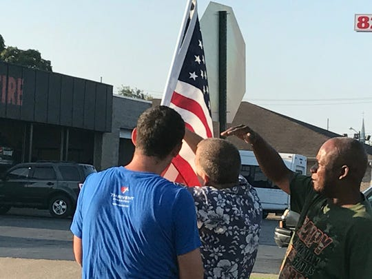 Matt Sauer, left, David McGruder, center, and Bennie Stone, right, working to restore American flag to its proper position.