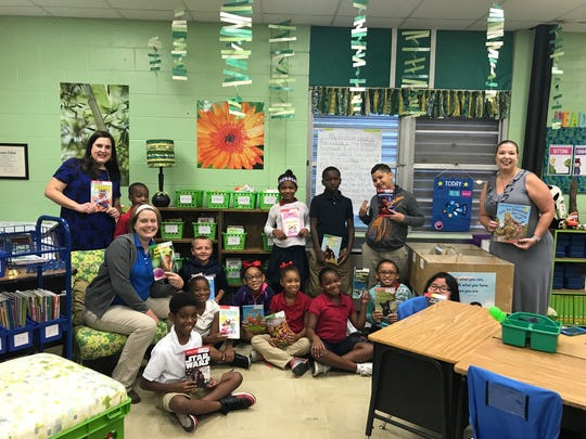 Patricia Thompson and Jennifer Middlebrooks of Cox Communications pictured with Laura Downing (seated) and her third grade class at Carencro Heights Elementary.