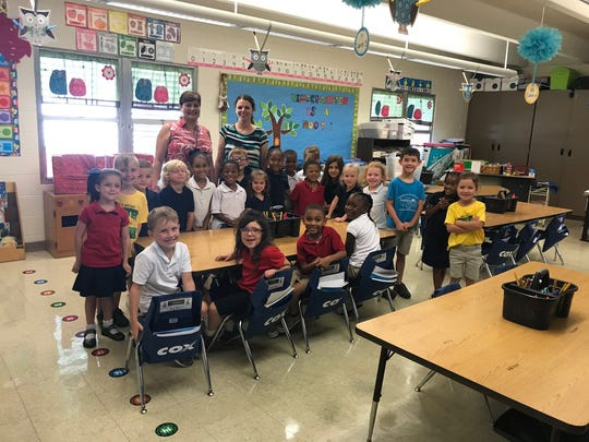 Katharine Drexel Elementary Principal Denise Soileau and Julie Martin, kindergarten teacher, pictured with a kindergarten class and their seat sacks at Katharine Drexel Elementary.