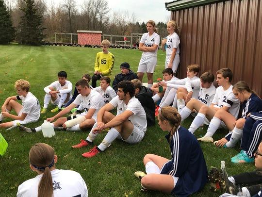 Marshfield Columbus Catholic coed soccer players listen