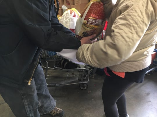 The handoff of a free turkey at Bidwell Riverside Center, a food pantry in Des Moines.