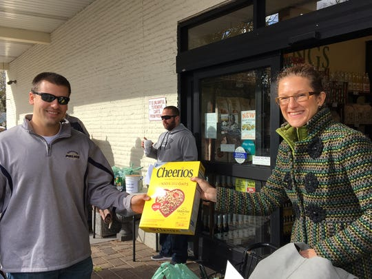 Morristown Police Officer Bryan Holmes accepts a food contribution from Kings shopper Priscilla Elms during PBA 43's 'Fill A Cruiser' campaign on Nov. 19, 2017.