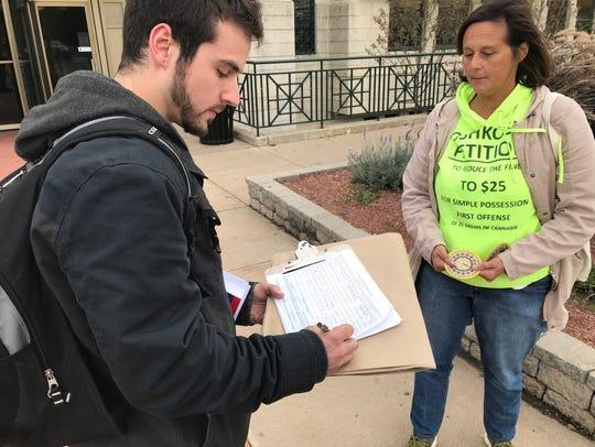 Caleb Kofler signs a petition to reduce Oshkosh's marijuana