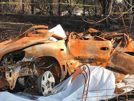 A burned out car destroyed in the fires that swept