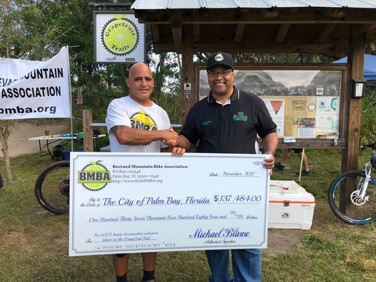 "Brevard Mountain Bike Association President Glenn ""Vader"" Hawks (left) presents a ceremonial check to Palm Bay Mayor William Capote commemorating $137,484 in donated volunteer labor."